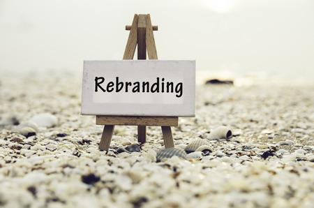 conceptueel beeld met het woord REBRANDING op wit canvas frame met houten statief staan. Vage Clamshell en kokkels achtergrond. Stockfoto