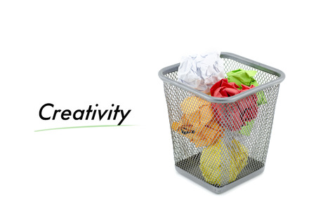 to thrash: conceptual image with word CREATIVITY over crumple paper in metal dustbin and isolated white background Stock Photo