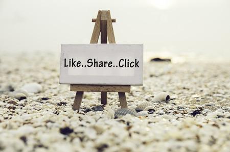 쉐어와 같은 단어로 개념적 이미지 나무 삼각대 스탠드와 흰색 캔버스 프레임에 클릭하십시오. 조약돌 껍질 및 cockles 배경입니다.