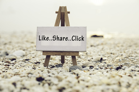 conceptual image with word LIKE SHARE CLICK on white canvas frame with wooden tripod stand.Blurred Clamshell and cockles background. Stock Photo