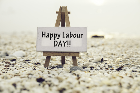 conceptual image with word HAPPY LABOUR DAY on white canvas frame with wooden tripod stand.Blurred Clamshell and cockles background.