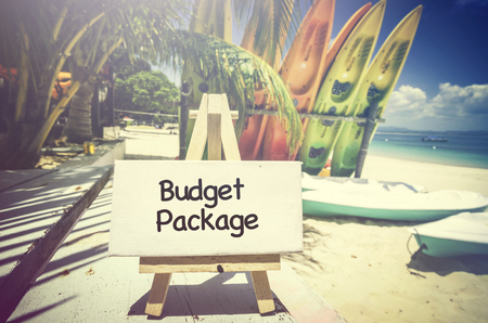 holiday budget: conceptual image with word BUDGET PACKAGE on white canvas frame and wooden tripod.