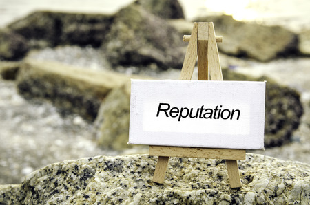 popularity: conceptual image with word REPUTATION on white canvas and wooden easel.Blurred rock and beach background at sunset.