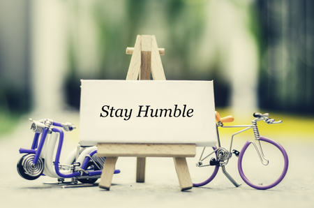 humble: Inspiration quote   stay humble with blur bokeh, easel,wired handcrafted scooter and bicycle background ,Motivational typographic.