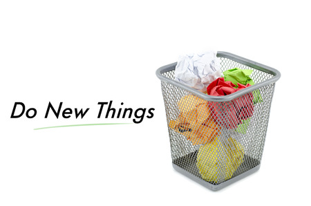 wastepaper basket: conceptual image with word DO NEW THINGS over crumple paper in metal dustbin and isolated white background