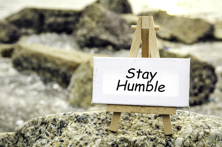 humilde: imagen conceptual con la palabra PERMANECER HUMILDE sobre lienzo blanco y caballete de madera. Fondo borroso de rock y playa al atardecer. Foto de archivo