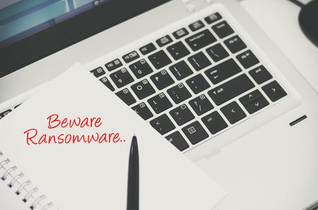 Cyber security concept, handschrift woord beware ransomware op wit papier over laptop background.color toon toegepast