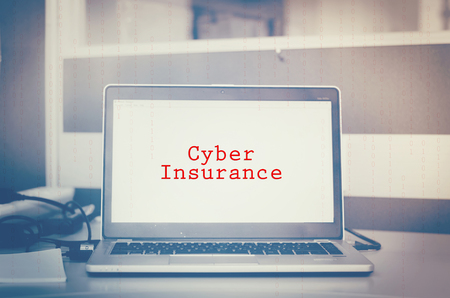 Red word, cyber insurance display on laptop screen. binary code and blurred background. cyber security metaphor concept