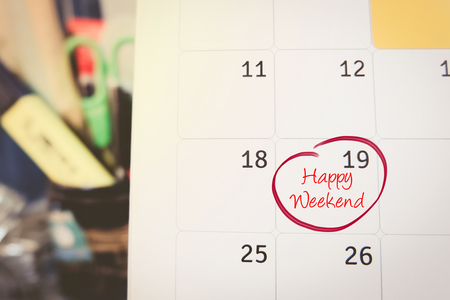 memo: handwriting word happy weekend on calendar over blurred background.selective focus shot