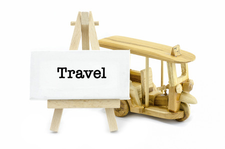 word travel on white canvas frame and wooden easel, isolated white background. iconic thailand public transport,called tuktuk