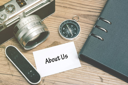 enquiry: ABOUT US word on white card. Vintage camera, miniature skateboard, compass and notebook on wooden floor background