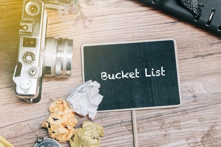 HET woordconcept van de EMMERLIJST met uitstekende camera, verfrommelt document, kompas en ontwerpersboek op houten vloer. Stockfoto