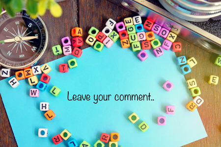 LEAVE YOUR COMMENT word on blue paper with compass, vintage camera and alphabetical block ideal for education and support concept