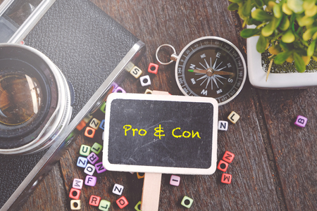 contra: Word PRO AND CON on wooden signage concept with vintage camera and compass decorative background