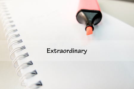 word EXTRAORDINARY on white book with highlighter pen ideal for business success concept