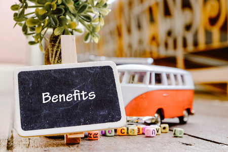 BENEFITS word concept, wooden signage over green artificial plant and minivan toy with retro color Stock Photo