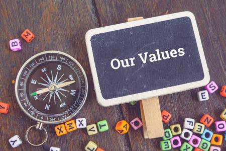 Business en ondersteuning concept afbeelding, word ONZE WAARDEN boven bovenaanzicht plat leggen houten signage en kompas op houten background.selective focus shot