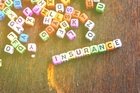 insurer: conceptual image with INSURANCE word block over wooden background Stock Photo