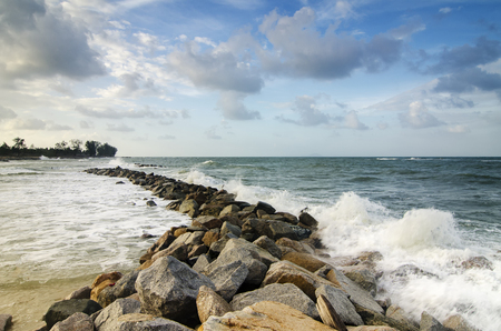 Beautiful nature, splashing wave while hitting the rock at the beach. cloudy blue sky background