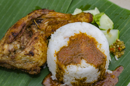 authentic malaysian dish, steam rice served with deep fried chicken leg, cucumber and chili paste on banana leaf.selective focus shot
