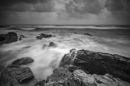 shorelines: Black and white image, beautiful nature wave hitting the rock over dramatic cloudy sky