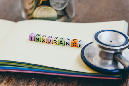 conceptual image with INSURANCE word block on note pad.coin in glass jar and used stethoscope. soft focus background Stock Photo