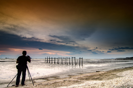 undentified man taking foto during sunset moment near the beach.magical sky color and low tide water