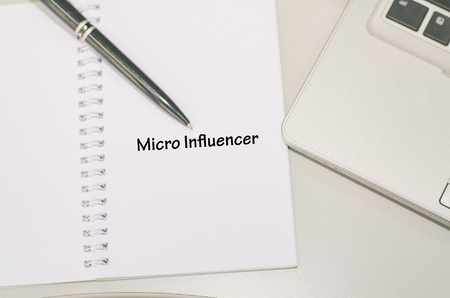 Business concept, word MICRO INFLUENCER over notepad, black pen and cropped laptop image