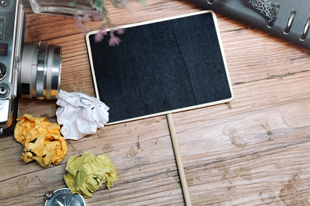 compas: travel and vacation concept, vintage camera, crumple paper,compas and planner book layout on wooden floor.