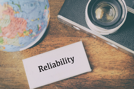 personal decisions: Word RELIABILITY with globe and vintage camera, ideal for marketing and business success concept Stock Photo