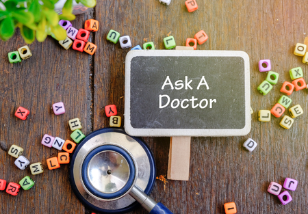 urologist: ASK A DOCTOR word for healthy and medical concept. Alphabet block, stethoscope on wooden background