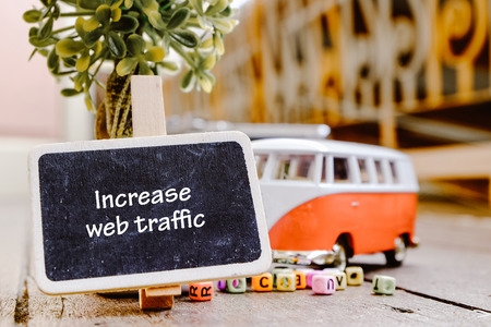 submit search: INCREASE WEB TRAFFIC word concept, wooden signage over green artificial plant and minivan toy with retro color Stock Photo