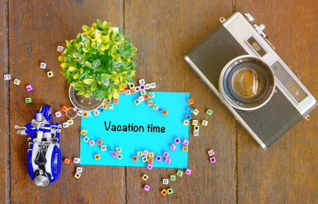 VACATION TIME word concept,top view notepad, artificial plant, handfrafted scooter and vintage camera on wooden table with alphabetical block Stock Photo