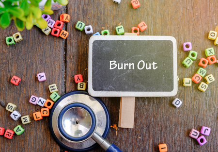 urologist: BURN OUT word for healthy and medical concept. Alphabet block, stethoscope on wooden background Stock Photo