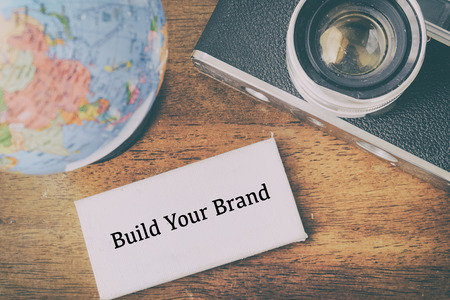 Word BUILD YOUR BRAND with globe and vintage camera, ideal for marketing and business success concept Stock Photo