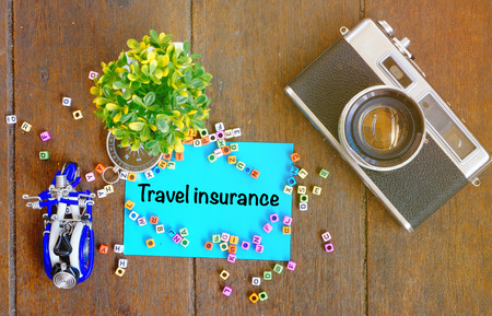 TRAVEL INSURANCE word concept,top view notepad, artificial plant, handfrafted scooter and vintage camera on wooden table with alphabetical block