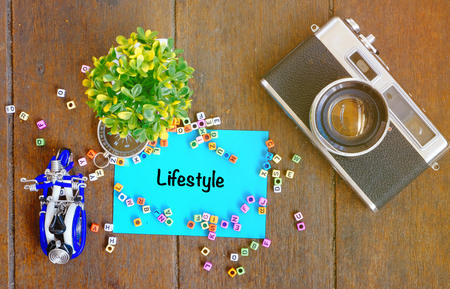 LIFESTYLE word concept,top view notepad, artificial plant, handfrafted scooter and vintage camera on wooden table with alphabetical block