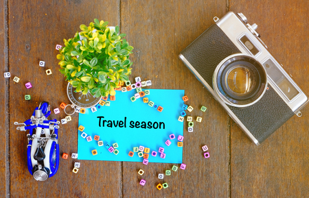 TRAVEL SEASON word concept,top view notepad, artificial plant, handfrafted scooter and vintage camera on wooden table with alphabetical block