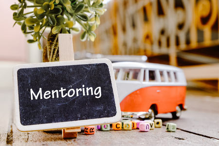 MENTORING word concept, wooden signage over green artificial plant and minivan toy with retro color