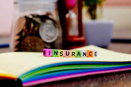 insurer: conceptual image with INSURANCE word block on note pad.coin in glass jar with soft focus background
