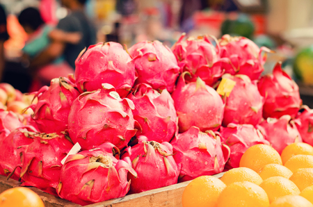 Exotic tropical fruit, dragon fruit or pitaya display for sell in market.selective focus shot. image may contain noise and grain due to available light shot