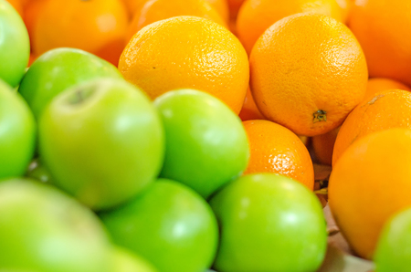 beautiful color combination, orange and green apple background display at market stall. selective focus shot Stock Photo
