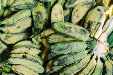 defocus shot of exotic tropical fruit, green banana display at market stall. selective focus shot.image may contain some grain and noise.