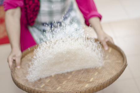 housewife winnowing rice by using bamboo basketwork for separate between rice and rice husk.selective focus shot Stock Photo