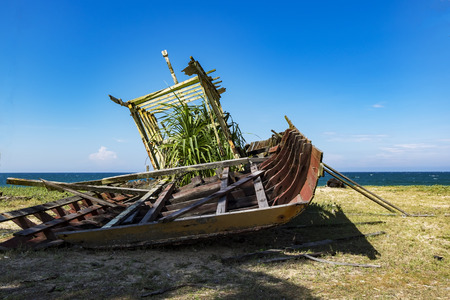 Abandon shipwreck near the sea shore under blue sky background and bright sun Stock Photo