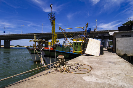 trawler net: traditional fishing boats moored at the harbour over the bridge and blue sky background during mid day