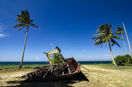 Abandon shipwreck near the sea shore under blue sky background and bright sun Stock Photo