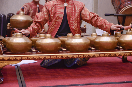 Man with Malay songket costume playing traditional music instrument called Gamelan. selective focus shot