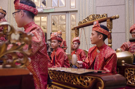 KUALA LUMPUR, MALAYSIA 12 JULY 2017: Group of Malaysian with songket performing Gamelan Orchestra and modern music instrument on hotel stage Editorial