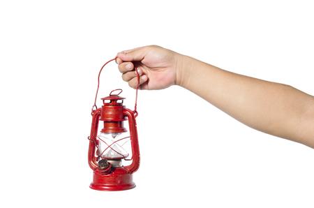 Hand holding red kerosene lantern lamp isolated on white background Stock Photo